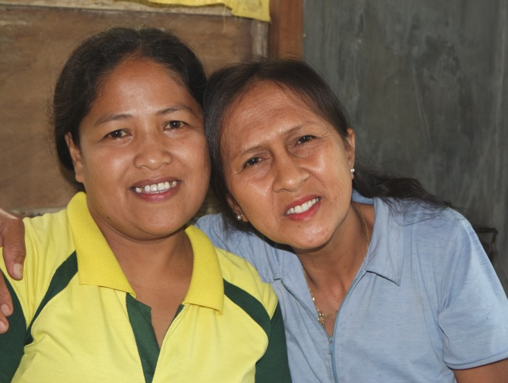 Estrellita Apale, right, embraces village health worker Jocelyn Canania.