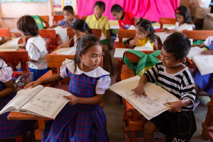Children reading in a classroom in the Philippines