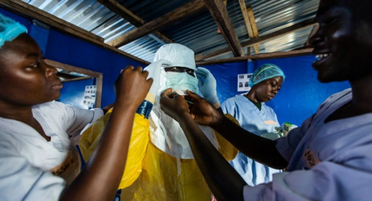A Liberian nurse prepares to go inside an Ebola patient ward to draw blood from confirmed patients for testing in Bong County la