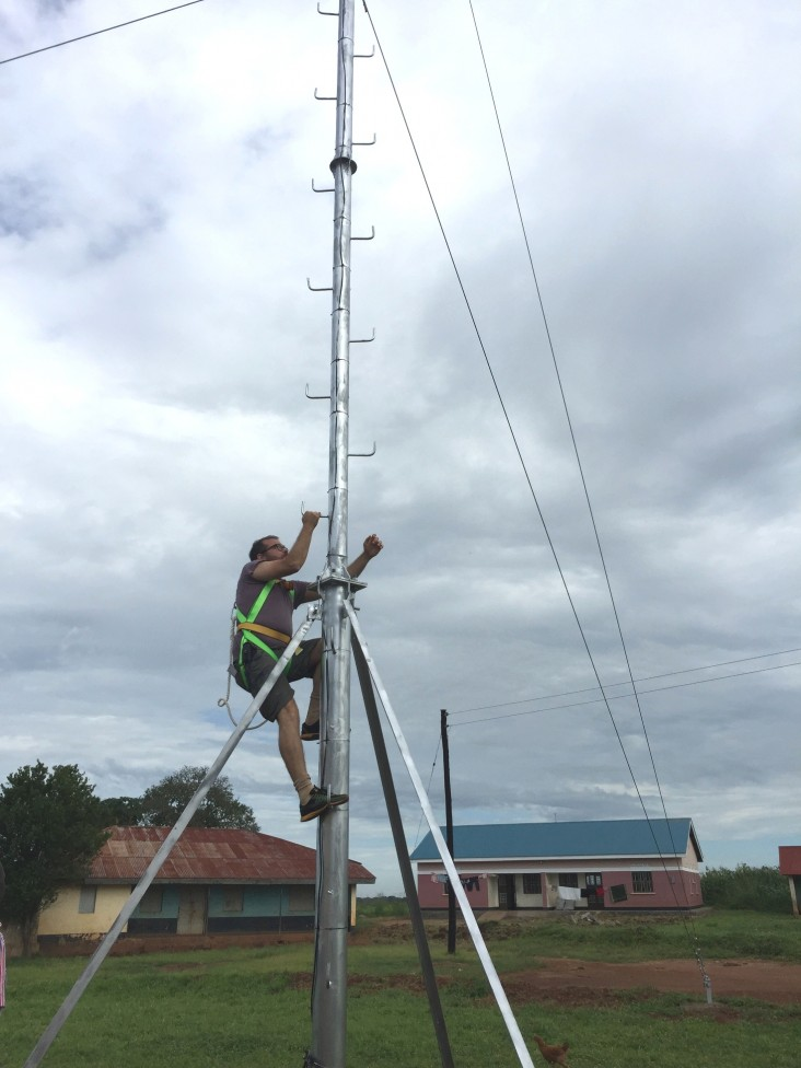 Chris Csikszentmihályi, director of RootIO Community Radio, climbs to set the transmitter at the first station.