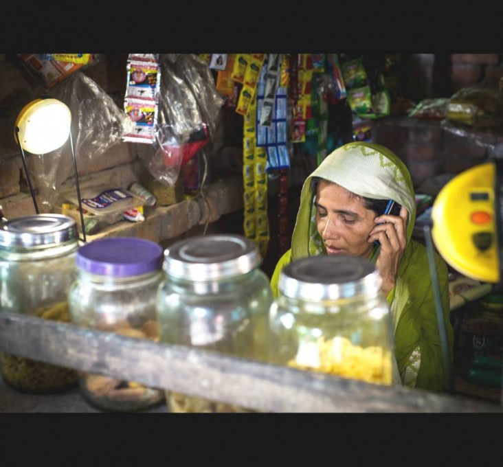 DCBS client Mamtaj Mondal in her shop lit by two solar lamps that can also charge her cell phone