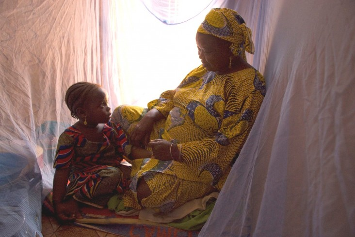 A Nigerian family uses protective malaria bed nets in their home.