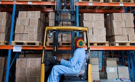 A worker stacks pharmaceuticals in a warehouse.
