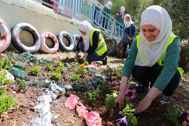 Students participating in locally-driven school beautification efforts targeting Irbid host communities.