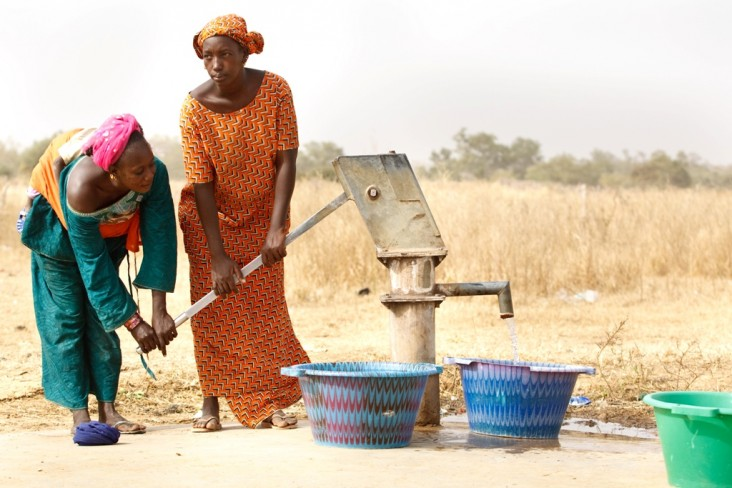 Two women pump water at a station