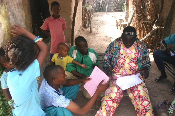 A community health worker reviews medical documents for Rougui Diallo's family.