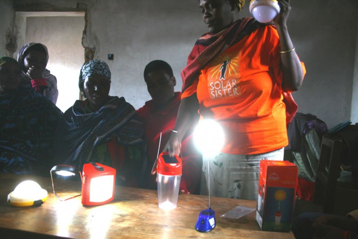Solar Sister Valentina Tiem from Tanzania demonstrates products to other women in her community. Image: -Solar Sister, 2014