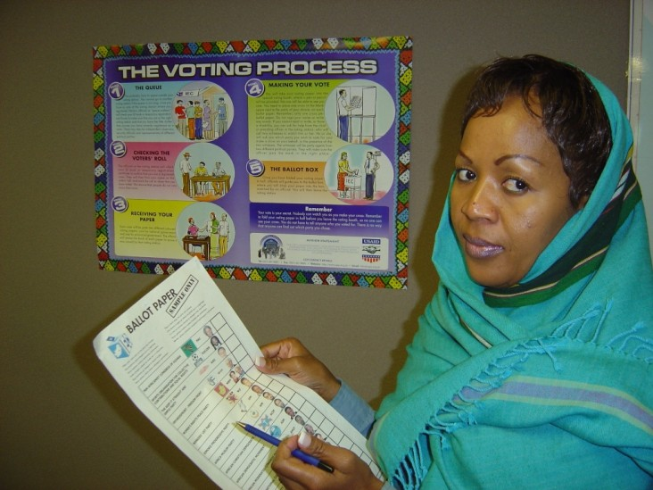 A woman holds up civic education materials in front of a poster.