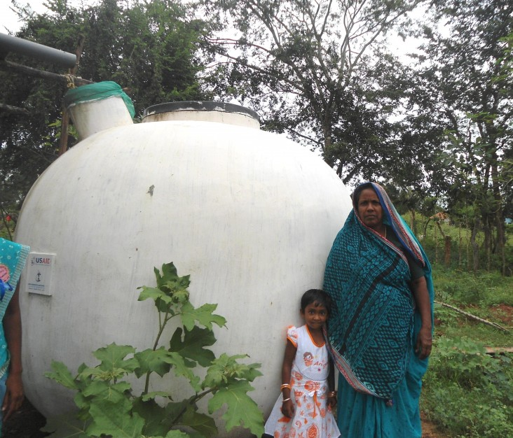 Abdulla Haleem's wife and granddaughter in front of their rainwater system