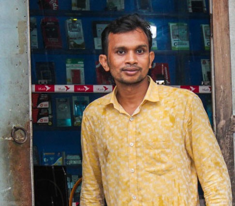 Saiful Islam greets visitors outside his electrical shop.