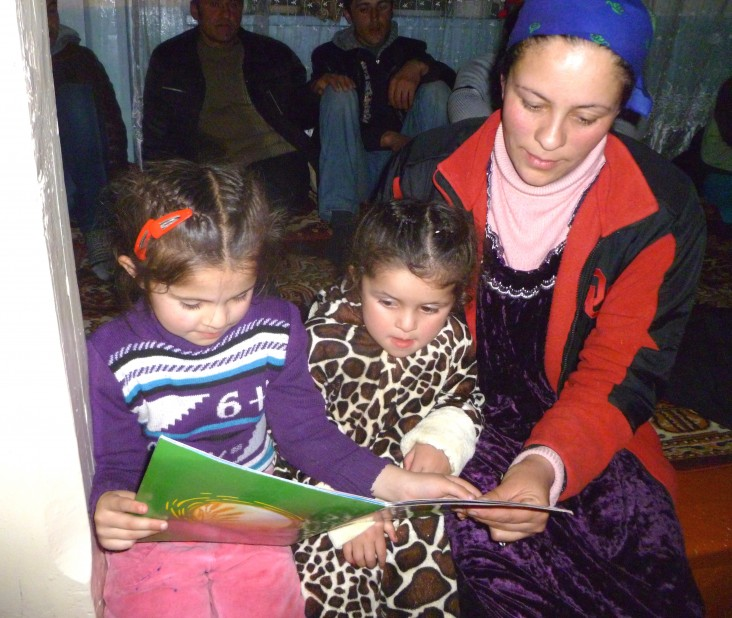 Amida Taqieva reads to her daughter Elvira, far left, and a friend in Deh, Tajikistan.