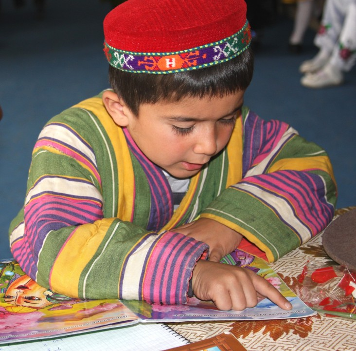 A boy reads from a USAID story book.