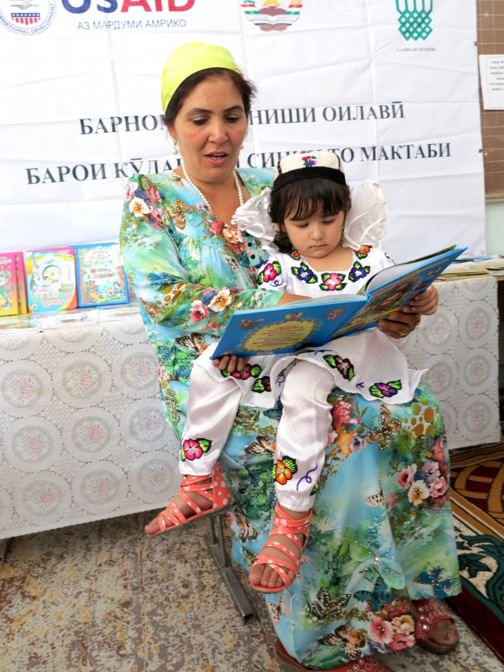 A teacher and student read together at a USAID event in Sarband, Tajikistan.