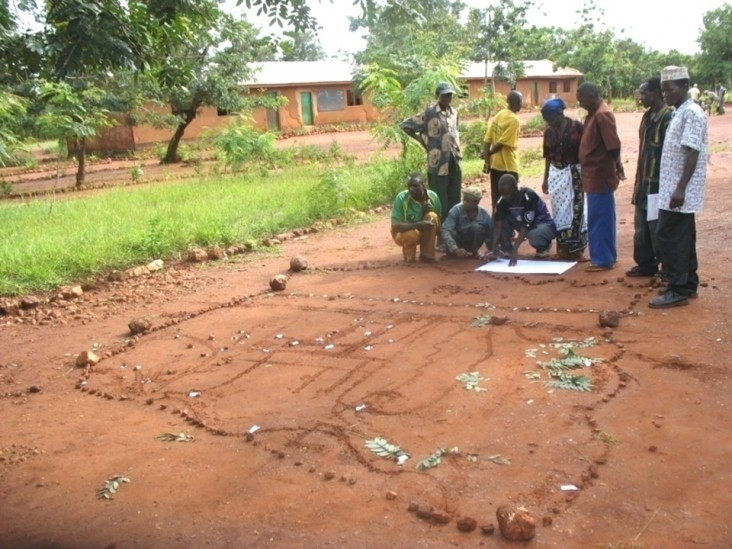 Villagers in Western Tanzania designate boundaries and landmarks using sticks and leaves to create a basic diorama of their vill