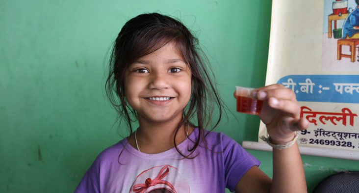 A young girl holds up a vial of a red liquid