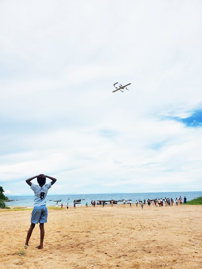 Villagers in Thotho watch as the drone flies overhead. / Ryan Triche, GHSC-PSM