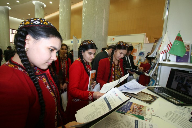 Young women review USAID materials at the Turkmenistan Ministry of Foreign Affairs expo.