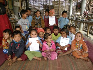 Nepalese children holding school exercise books produced by USAID