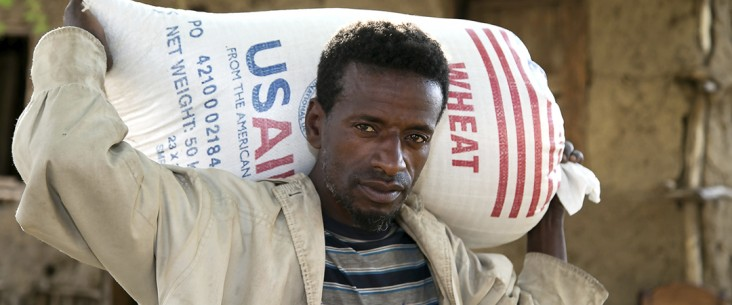 A man carries a bag of wheat from USAID
