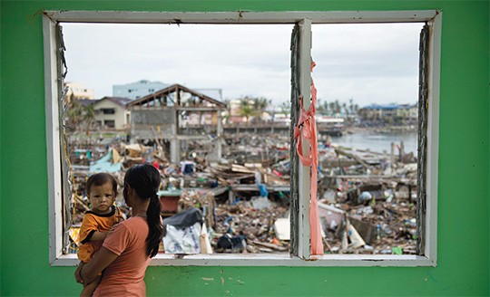 A victim from Typhoon Haiyan observes the devastated waterfront community in Tacloban. The Philippines loses up to $5 billion ev