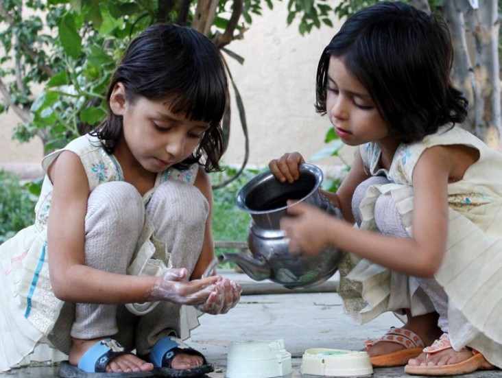 One little girl pours water over another little girls soapy hands.