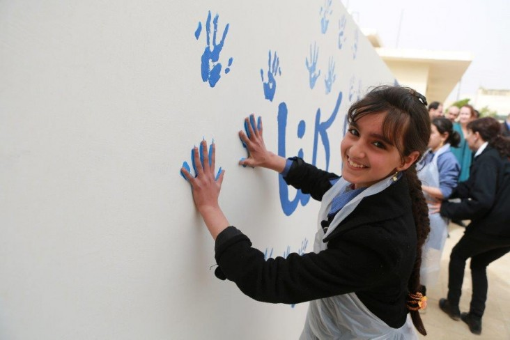 Students at an Irbid Governorate school stamp their hands on a cistern that will help the school build its own water reserves.