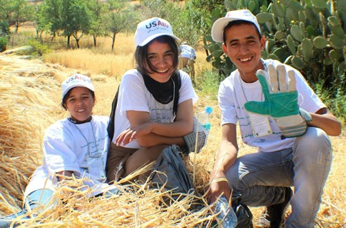Image of three young Moroccan environmentalists collecting solid waste.