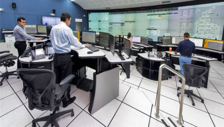 Independent system operator staff work at several computer workstations in a large room with a wall of computer displays to manage Colombia's national electricity system.