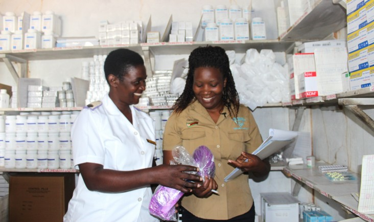 A staff member from a USAID partner organization, right, works with health care workers to determine stock levels of medicines and medical supplies.
