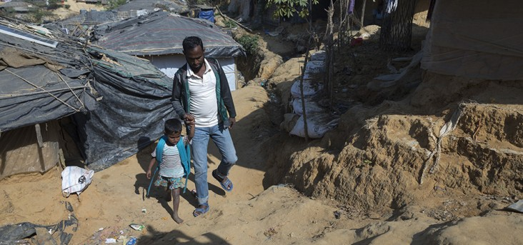 Jamal Hossain takes his daughter Yasmin Akhter to school at Kutupalong Refugee Camp, Cox's Bazar. Photo by Tapash Paul for USAID