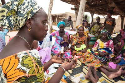 At a monthly community meal, a USAID volunteer shows women how to test salt to ensure it is iodized.