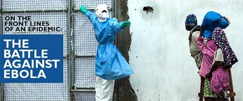 A health care worker in complete protection gear beckons to passer-bys.