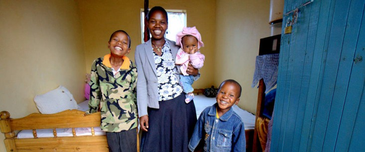 Tina, who is living with HIV, with her three children at her home in Tanzania.