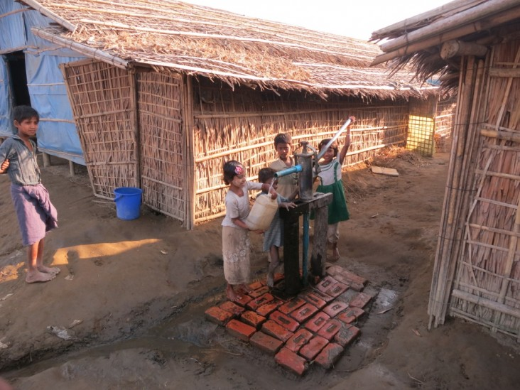 Displaced children using a water pump in Rakhine State, Burma.