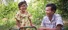 A man smiles with a child wearing glasses