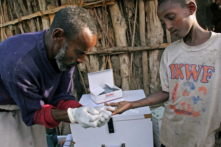 A Community Health Worker in rural Ethiopia tests a boy for malaria.