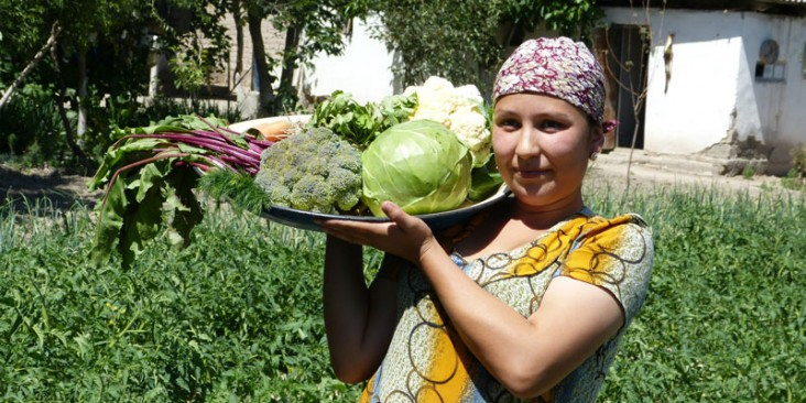 Habiba Tukhtaeva shows off the vegetables she grew in her family's kitchen garden with support from Feed the Future.