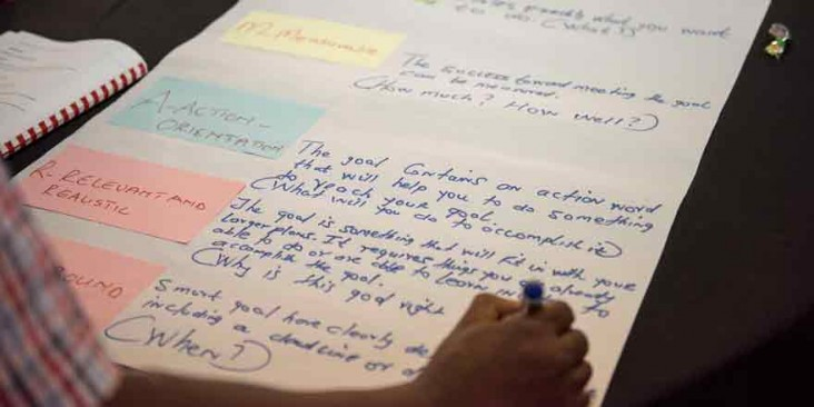 A hand writes of a paper with text and colored notes.