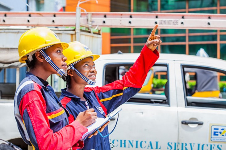 Two female line workers in Nigeria looking up
