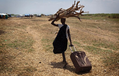 A South Sudanese woman walks with wood to reinforce her house in an isolated makeshift camp for internally displaced people in S
