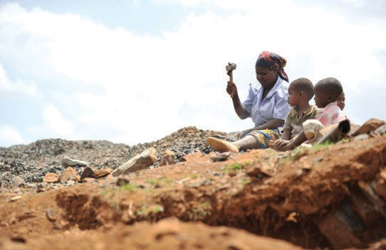 A Kenyan woman breaks stones for a local construction company at a quarry with her children. Women are more likely to be employe
