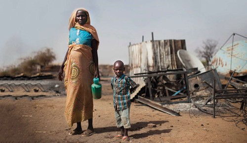 A displaced mother and her child inspect the remains of their burnt house in South Darfur. The United Nation's High-level Panel