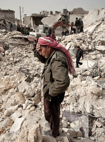 A Syrian man reacts while standing on the rubble of his house, while others look for survivors and bodies in the Tariq al-Bab di