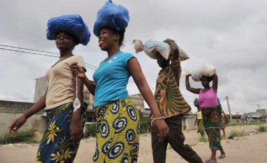 Women carry goods on their heads as they return from shopping in Abidjan. In Côte d'Ivoire, unmet family planning needs, combine