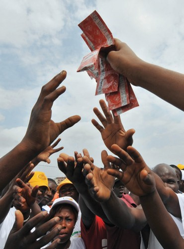 A young woman hands over condoms in a working district of Abidjan, Cote d'Ivoire, as part of an AIDS prevention program. Contrac