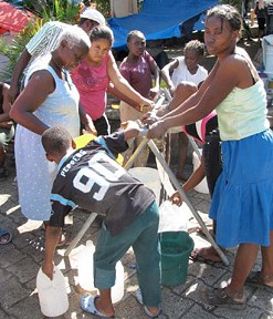 Camp residents filling water containers from a water-bladder fed tap stand.