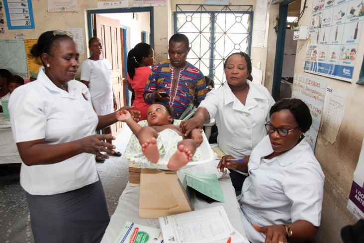 Nurses carry out standard checks to evaluate a child's health, noting his weight and other measurements. Photo credit: Frank Ribas for Communication for Development Ltd.