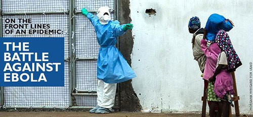 A masked medical person ushers patients in to an Ebola treatment center