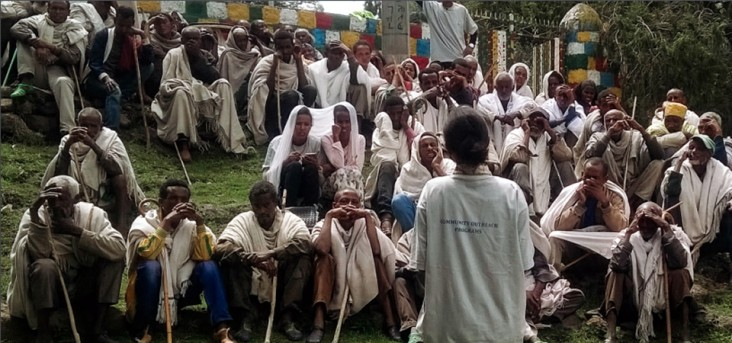 A young health worker addresses a group of elders as part of a global health security agenda outreach program.