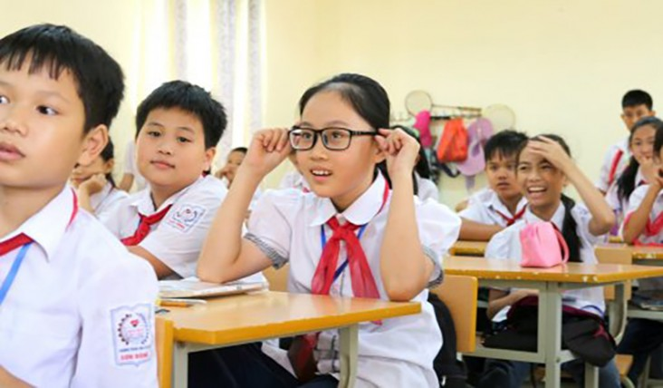 A young girl puts on glasses, surrounded by other students.